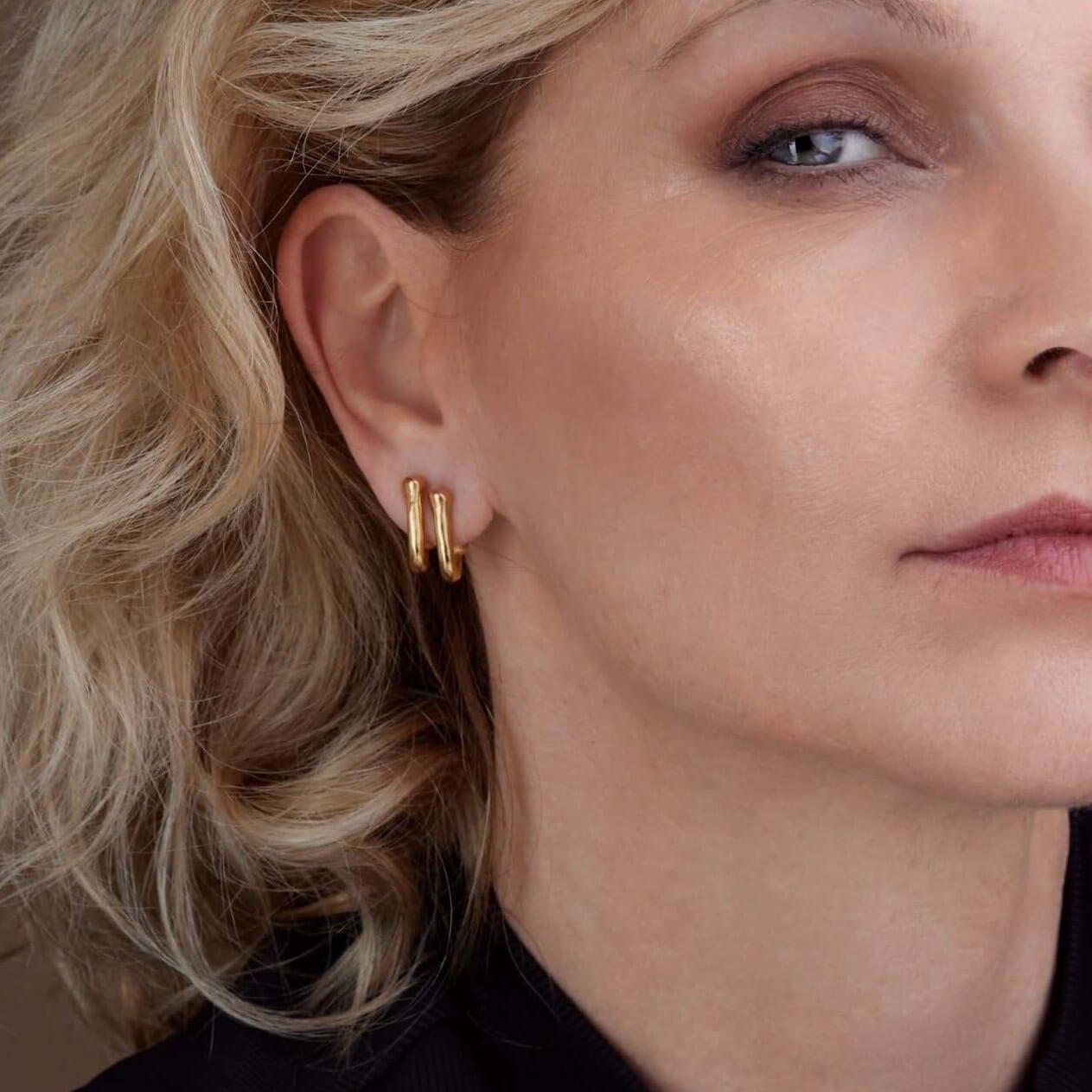 שני עגילים חובקים על אוזן ימין של הדוגמנית, סטודיו לתכשיטים הילה אלון